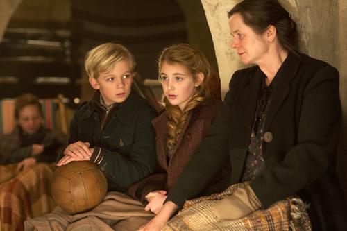 Im Luftschutzbunker erzählt Liesel (Sophie Nélisse) zur Ablenkung Geschichten - nicht nur Rosa (Emily Watson, rechts) und Rudi (Nico Liersch) lauschen gespannt.