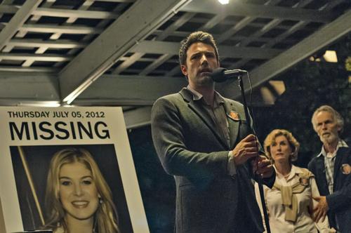 Der vor Kameras stets ungeschickt agierende Nick (Ben Affleck, links) bittet unter den strengen Augen seiner Schwiegereltern Marybeth (Lisa Banes) und Rand (David Clennon) die Bevölkerung von Missouri um Mithilfe bei der Suche nach seiner Frau Amy.