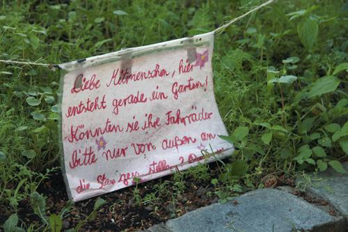 Liebe Mitmenschen, hier entsteht gerade ein Garten! Könnten sie ihre Fahrräder bitte nur von außen an die Stange stellen.