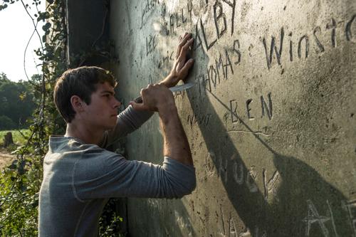 Neuankömmling Thomas (Dylan O'Brien) ritzt nach den Regelwerk seiner neuen Zwangsgemeinschaft seinen Namen in die Felswand.