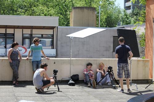 The making of: Fünf Menschen vor einer Betonwand. Jungregisseur Schneckenburger hockt gebannt hinter der Kamera.
