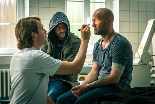 Erik (Jürgen Vogel, rechts) lässt sich vom Arzt (Fabian Hinrichs, links) untersuchen. Henry (Moritz Bleibtreu) ist immer dabei, aber für alle außer Erik unsichtbar.