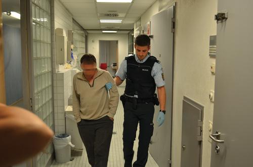 Abgeführt: Ein Beamter bringt den zugedröhnten Mann in die Ausnüchterungszelle.